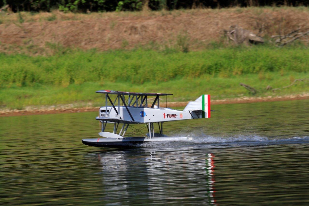 Per un istante si vede l'immagine dell'aereo, riflessa nelle acque limpide del Ticino, allontanarsi dal solco lasciato dallo scarpone, la coda tricolore specchiata svanire nel fiume perdendosi nelle sue profondità, intanto che il Piaggio prende quota